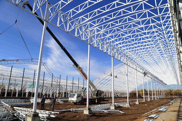 工人利用晴好天气进行钢结构吊装.